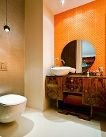 Antique, half-height cabinet on legs in orange-tiled niche in modern bathroom