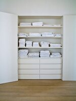 Stacked, white linen on shelves above drawers in white, open cupboard in niche