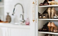 High-heeled shoes in shoe rack with open door; blurred kitchen counter in background