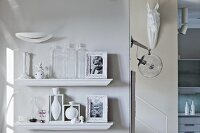 Decorative vessels and framed, black and white photographs of children on two floating shelves; lamp and horse head sculpture at foot of staircase