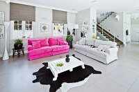 Pink sofa and pale sofa in large interior with staircase in background