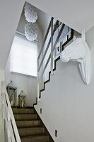 Staircase with vintage lanterns, retro pendant lamps and white horse-head sculpture