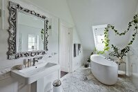 Mirror with patinated frame above washstand; free-standing bathtub below garland of ivy