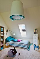 Cat playing in teenager's attic bedroom with bed on floor under skylight