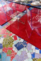 Transparent plastic chairs on red rugs and mosaic-style floor