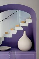 White clay vase artistically arranged on purple cabinet in arched niche in front of staircase