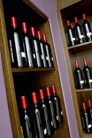 Dark wine bottles with red foil capsules in wood-clad niches in wall painted lilac