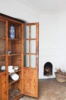 Old, glass-fronted cabinet with open door in interior with terracotta floor and open fireplace built into wall