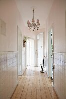 Elegant, narrow hallway with chandelier, half-height tiled walls and rustic wooden floor