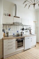 Functional kitchen with white units and spidery, 50s-style pendant lamp in rustic setting