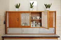 Potted house plants on 50s kitchen dresser with open door showing white crockery inside