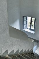 Open window in white stairwell with grey steps
