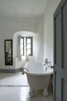 Simple bathroom with antique bathtub and white floor tiles