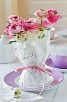 Woman's name on wrapped ranunculus bouquet with pink ribbon on plate