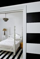 Black and white striped wall and view through open door of bed with white-painted wooden frame on black and white striped rug