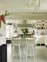 Spacious kitchen with central island, white walls and white-painted furniture