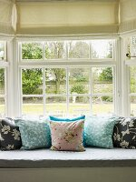 Cushions on window seat with view of garden