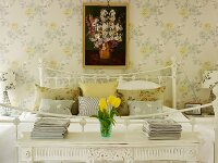 Romantic bedroom with bedside tables, floral wallpaper and picture of flowers