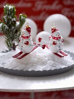Snowman baubles on plate with artificial snow