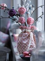 Arrangement of artificial flowers in fabric-wrapped vase on window sill