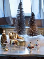 Christmas baubles and miniature gilt chaise longue in front of Christmas tree ornaments