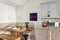 Blue-red typeface behind a square dining table with corner bench and simple kitchen with serene Shaker style color scheme