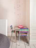 Sitting area with colorful wicker chairs and pink coffee service in a child's room