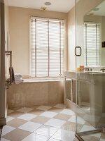 Elegant bathroom with marble clad tub and diagonal tile pattern on floor
