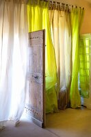 Airy curtains in various shades of green and open, rustic wooden door