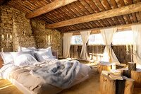 Double bed and tables made of tree trunks on sand floor in barn-like interior with rough stone walls and gathered curtains at window