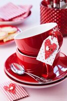 Two stacked teacups and tag with heart for romantic message