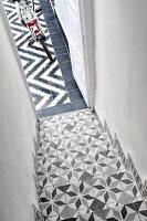 Staircase with traditional, Moroccan-style patterned tiles merging into modern, graphic, black and white pattern of courtyard floor tiles