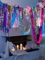 Garlands hanging above white wire chair in front of fireplace with lit candles and decorative honeycomb paper balls