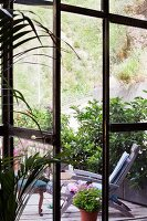 View of sun lounger on wooden terrace surrounded by foliage plants through open French windows