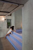 Exposed concrete walls and polished concrete floor contrasting with lavender stepped platform leading to sunken bathtub; woman lighting candles on edge of bath