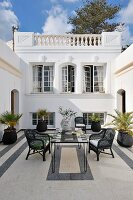 North African style courtyard with black and white theme with wicker chairs around a mosaic table and potted palms