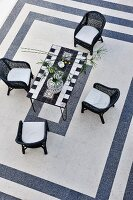 Wicker chairs around a mosaic table and black and white tile patterns (top view)