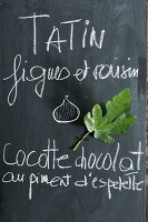 Hand-written menu and fig leaf on blackboard in kitchen