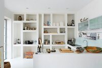 Large-scale fitted shelving with irregular compartments in minimalist white kitchen