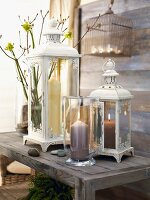 Lit candle in candle lantern in front of vintage-style lanterns on rustic wooden bench