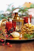 Red glass tealight holder, gilt lantern and pine cone decorations on platter
