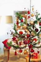Stylised Christmas tree decorated with various red and gold baubles