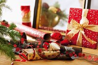 Rolls of wrapping paper and ribbons next to wrapped Christmas present with bow
