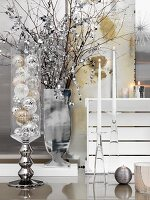 Christmas baubles in glass container, silver vase of decorated twigs next to candlesticks