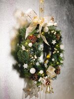 Festively decorated wreath with bow hanging on wall