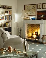 Open fireplace with tiled fireback in living room with white leather couch and maritime decor