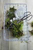 Wire basket with moss, aluminum wire, star-shaped cookie cutters and scissors