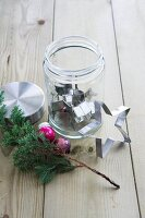 Star-shaped cookie cutter in a screw top jar, next to it a pine branch and Christmas ornaments