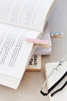 Decorated clothes pegs used as bookmarks
