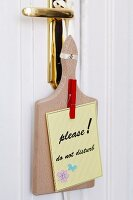 'Do not disturb' sign made from chopping board & clothes pegs